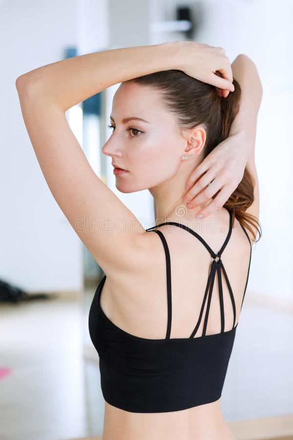 Woman posing doing exercises in fitness club wearing black top with stripes stock image