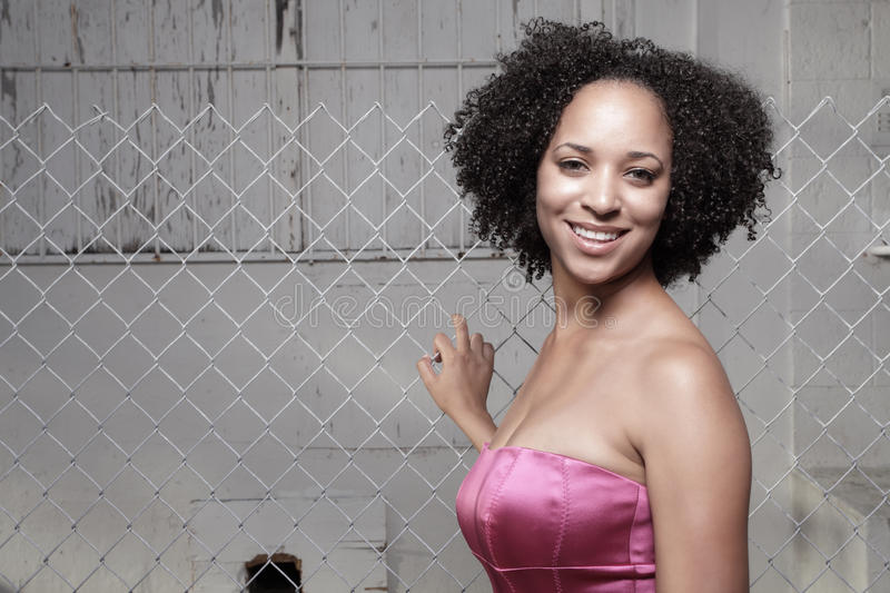 Woman posing by a fence. Attractive woman smiling and posing by a chain link fence in the city stock photography