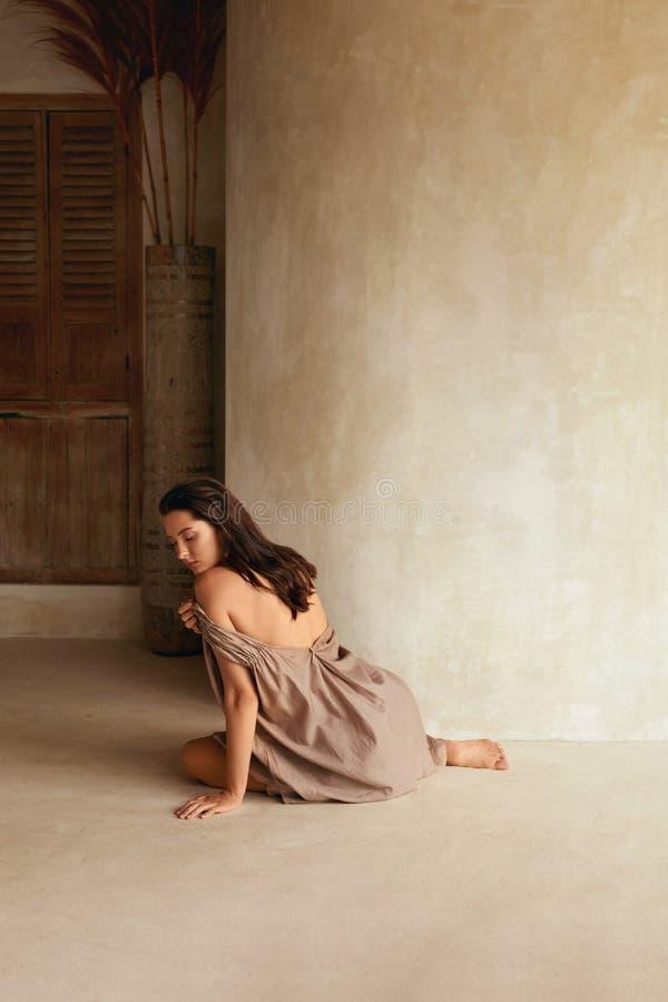 Woman Posing On Floor Outdoors. Rear View Of Beautiful Model In Seductive Dress Sitting On Terrace. Summer Portrait. stock photo