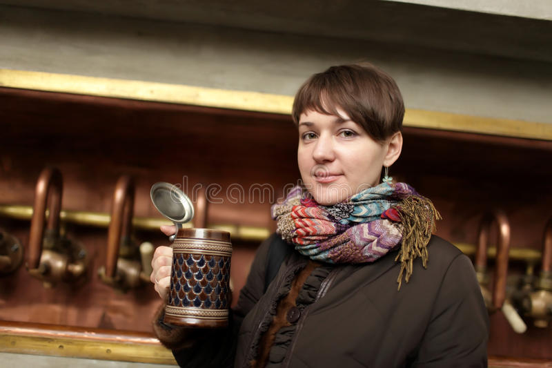 Woman posing with glass of beer. At an old brewery stock photo