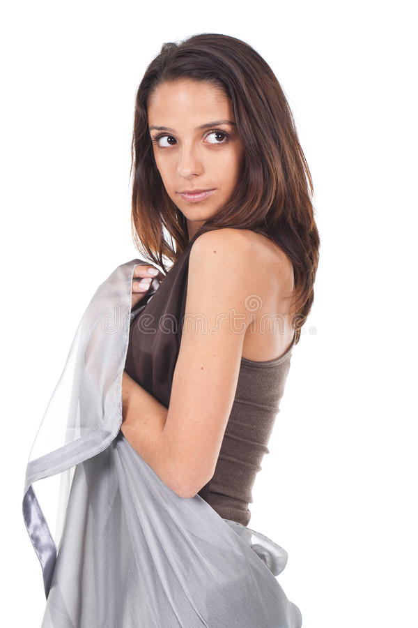 Woman posing with a grey scarf. Young and atractive woman posing wrapped in a grey scarf stock image