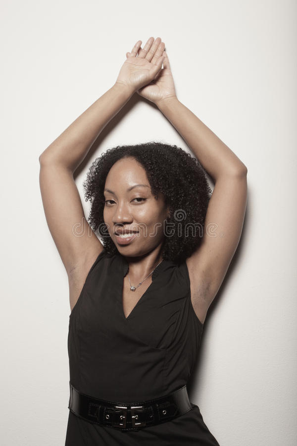 Woman posing with her arms above her head royalty free stock images