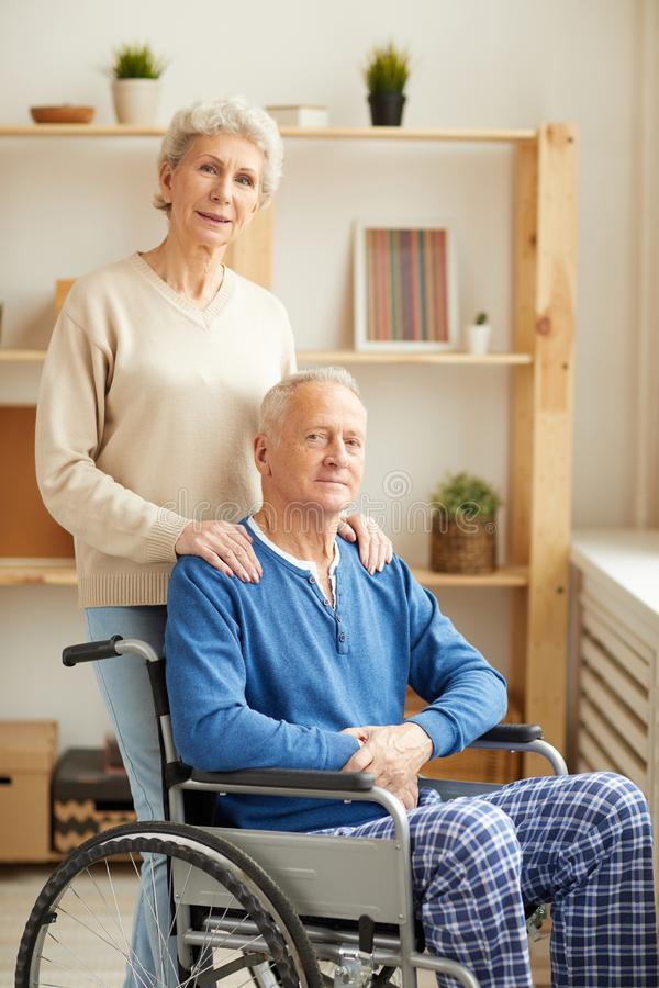 Woman Posing with Husband in Wheelchair royalty free stock photography
