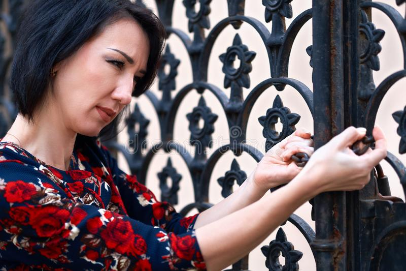 Woman posing near black wrought iron gates, holds the chain stock images