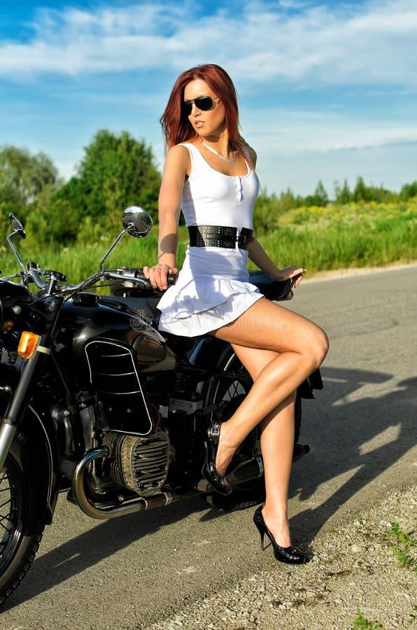 Woman posing near vintage motorbike royalty free stock image