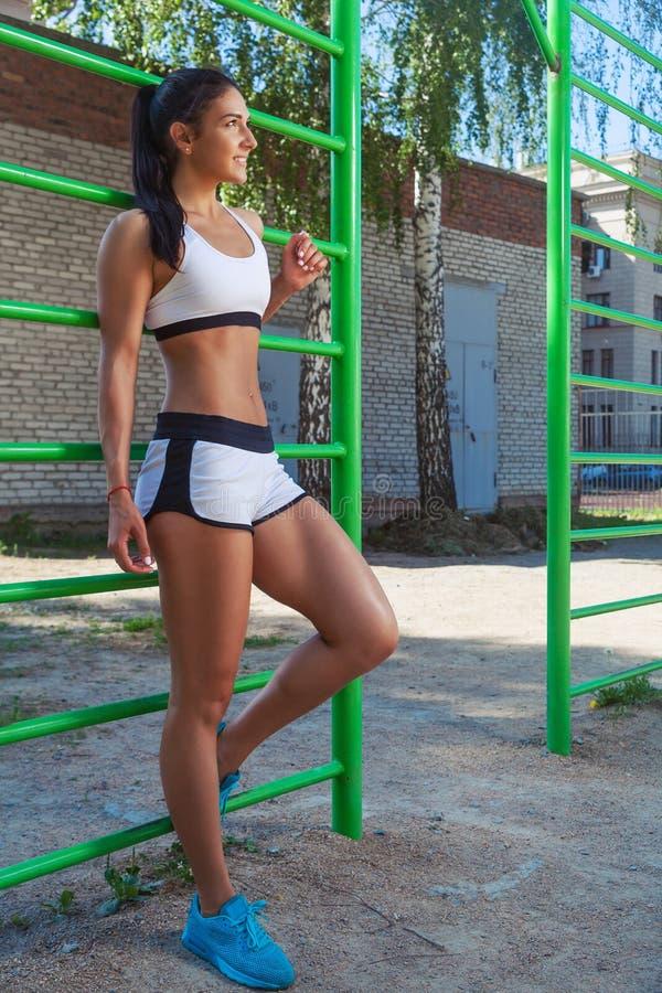 Woman posing next to sports horizontal bars royalty free stock image