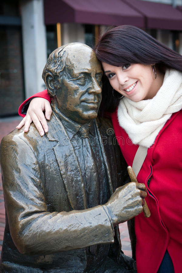 Woman Posing with Public Statue. Young woman puts her arm around the public Red Auerbach statue found in Bostons Quincy Market just outside of Faneuil Hall stock images