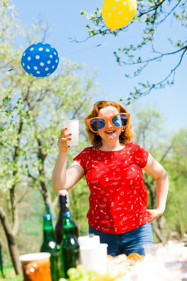Woman posing in red dress and big funny sun glasses on garden royalty free stock image
