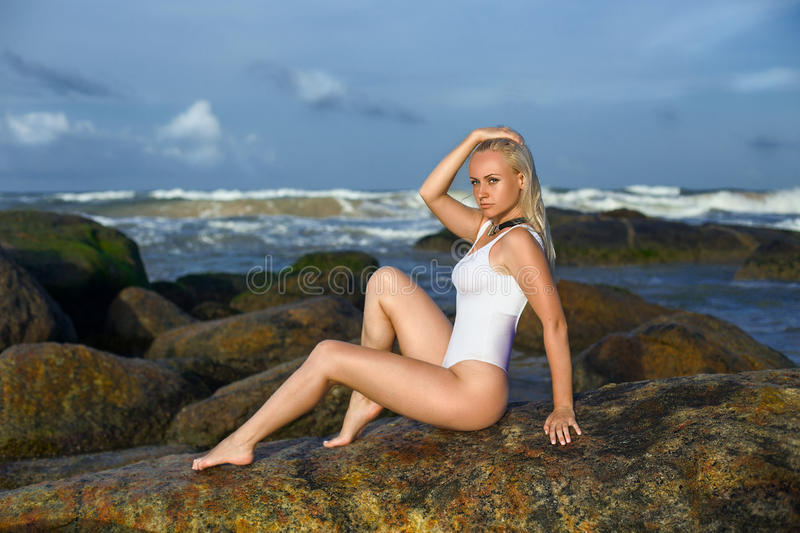 Woman posing on the rocks in the ocean stock photography