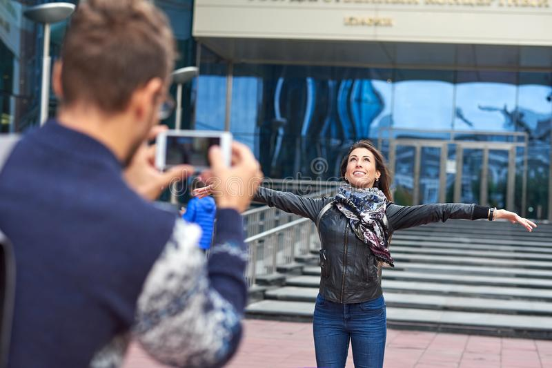 Woman posing for vacation photo in urban city tour. Couple of tourists making photo royalty free stock photography
