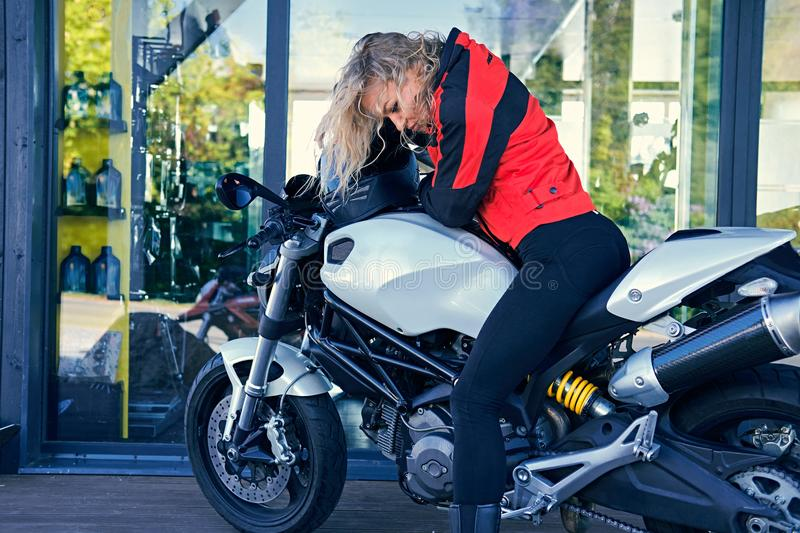 A woman posing with white speed motorcycle. stock images