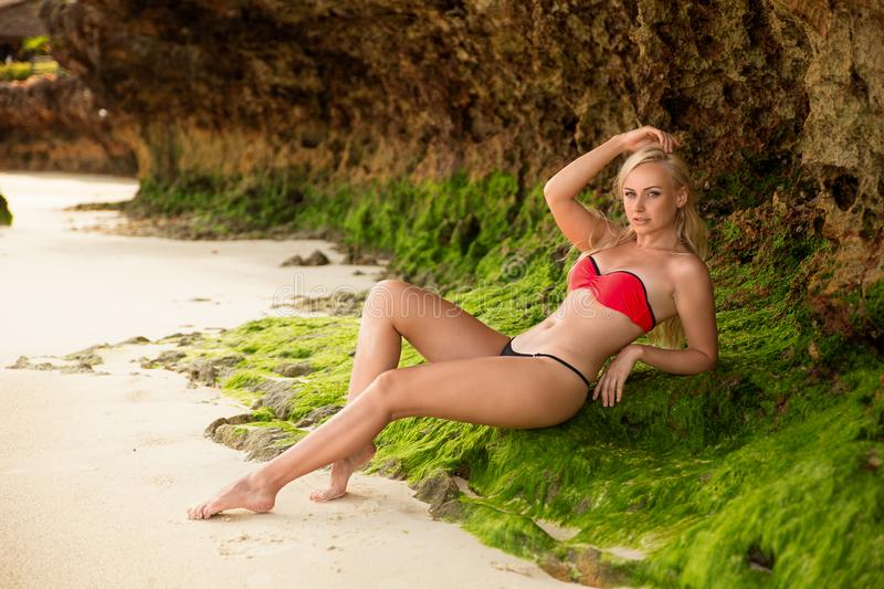 Woman posing on the Zanzibar`s white sand beach. Beautiful blonde woman in the red bikini posing near the rocks on the lonely evening beach with white sand stock photos