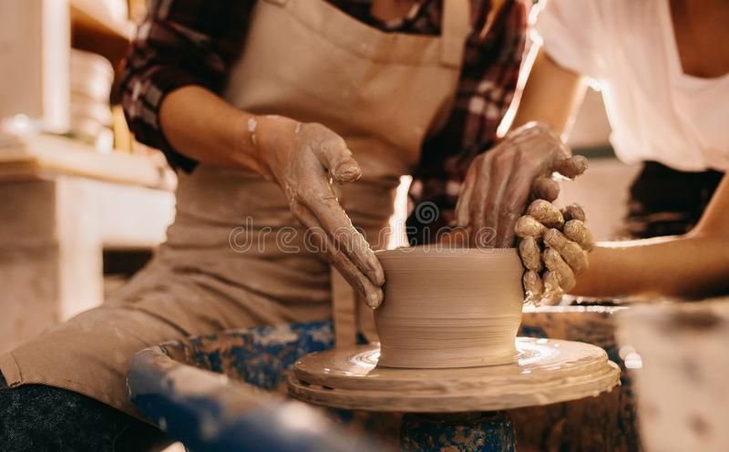 Two women at a pottery workshop making clay pots stock image