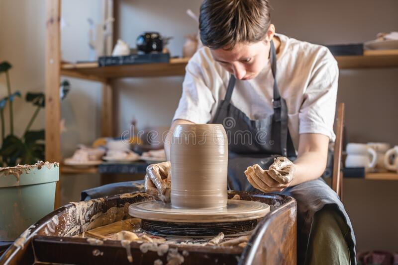 Woman potter working on Potter`s wheel making a vase. Master forming the clay with her hands creating jug in a workshop. Woman potter working on a Potter`s wheel stock photography