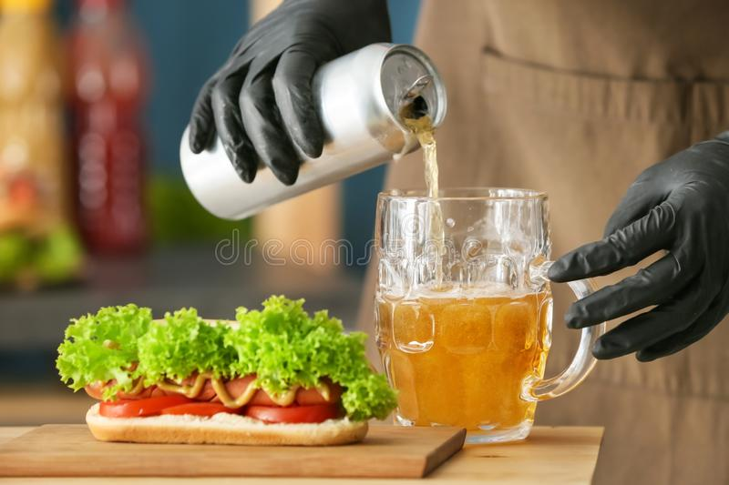 Woman pouring beer from tin can into glass mug on table with tasty hot dog stock photo