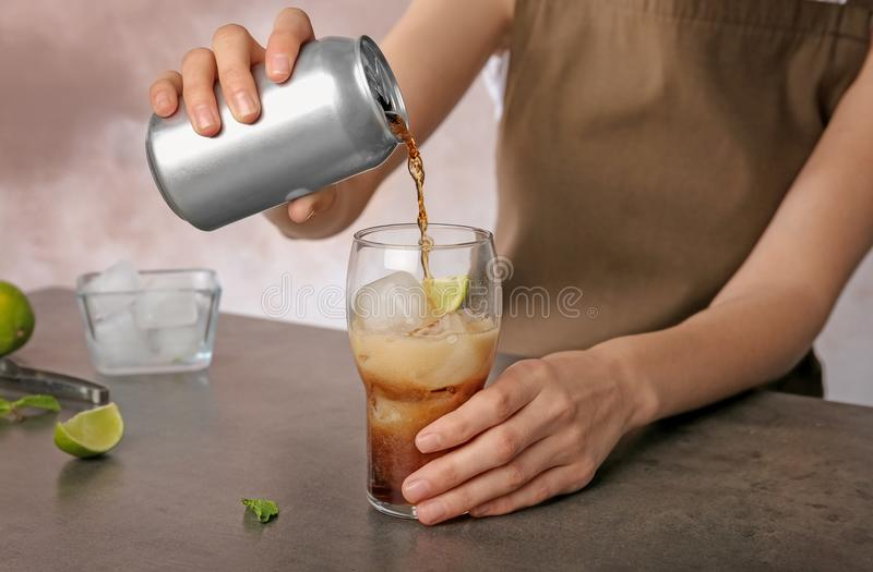 Woman pouring cola from tin can into glass. At table royalty free stock images