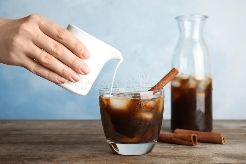 Woman pouring cream into glass of coffee with ice cubes. On table against color background stock photo