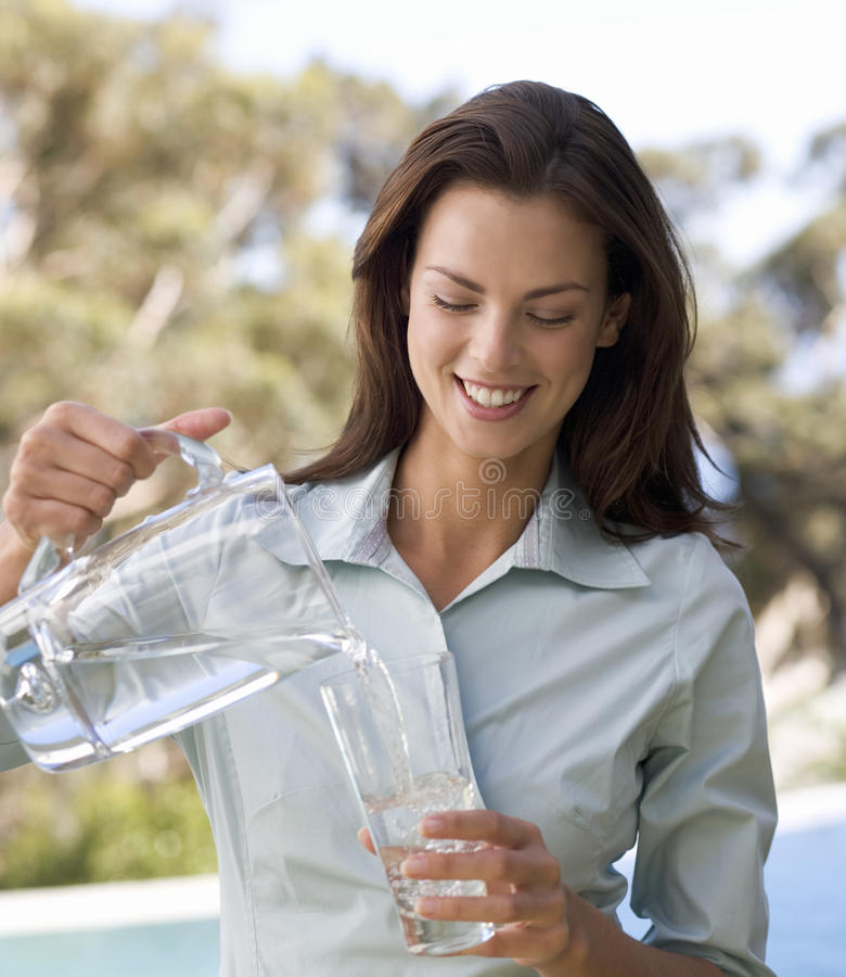 Woman pouring a glass of water royalty free stock images