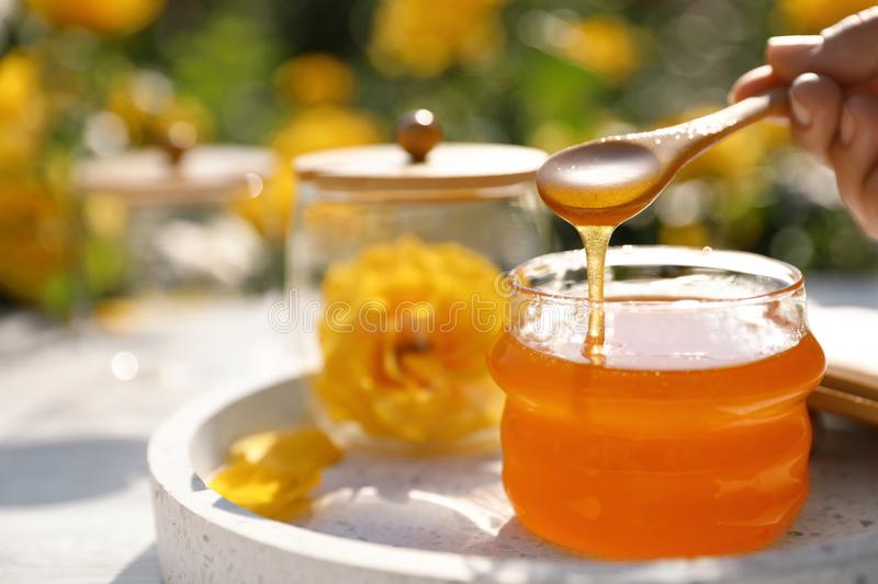 Woman pouring honey into glass jar at white wooden table. Space for text stock photography