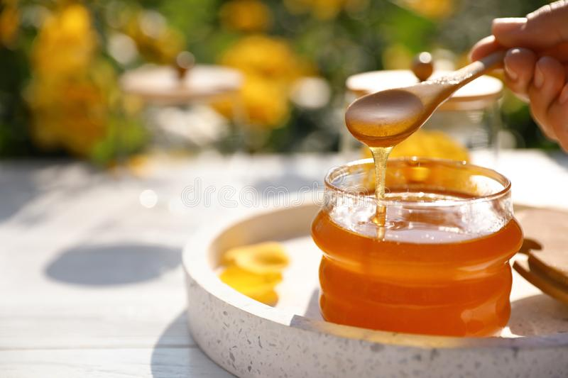 Woman pouring honey into glass jar at white wooden table, closeup. Space for royalty free stock photo