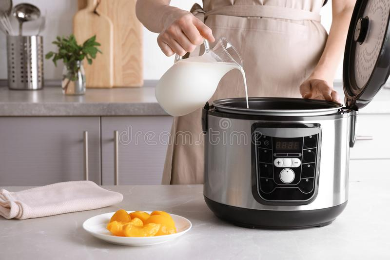 Woman pouring milk into modern multi cooker for making delicious yogurt at table. Closeup stock photography