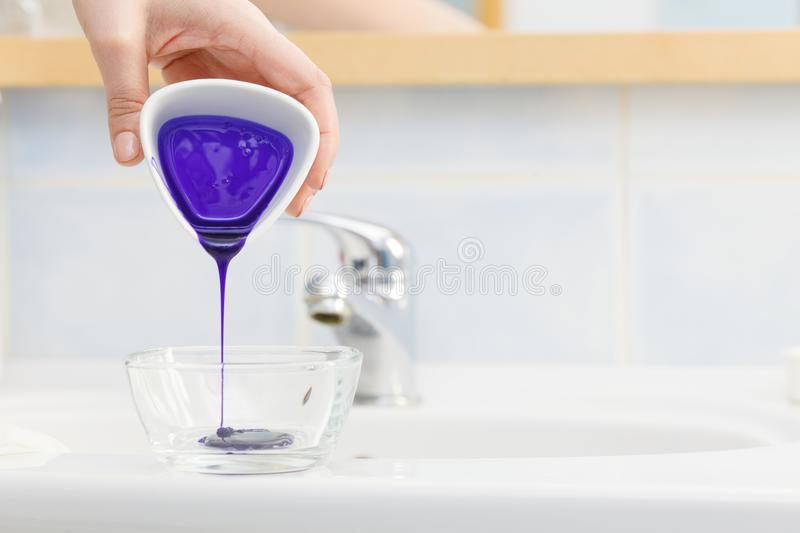 Woman pouring purple hair dye or shampoo. Toner into white bowl. Hygiene object concept stock photos