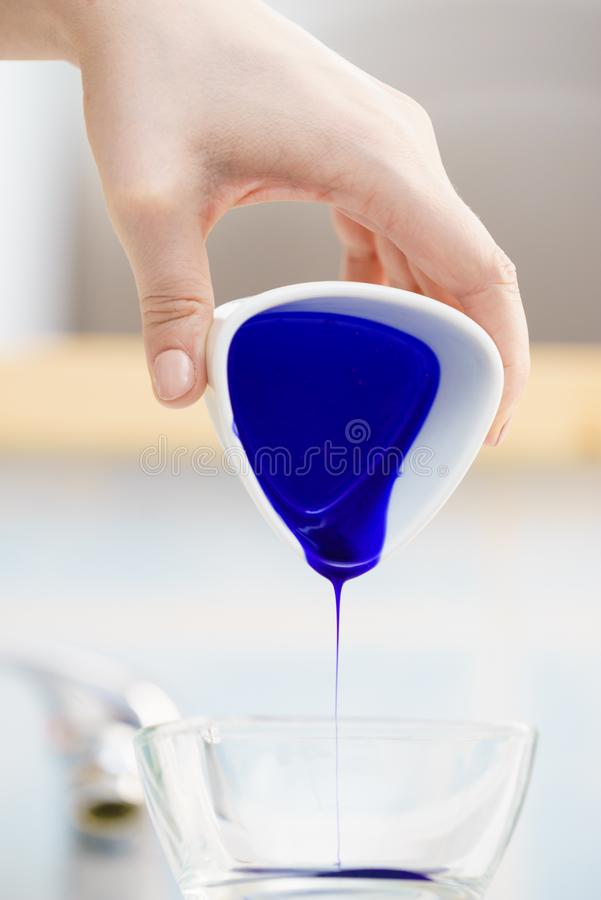 Woman pouring purple hair dye or shampoo. Toner into white bowl. Hygiene object concept stock photography