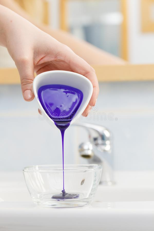 Woman pouring purple hair dye or shampoo. Toner into white bowl. Hygiene object concept royalty free stock image