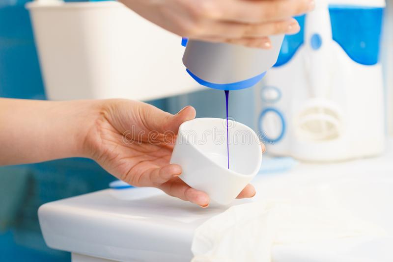 Woman pouring purple hair dye or shampoo. Toner into white bowl. Hygiene object concept stock image
