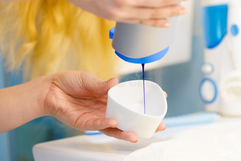 Woman pouring purple hair dye or shampoo. Toner into white bowl. Hygiene object concept royalty free stock photography