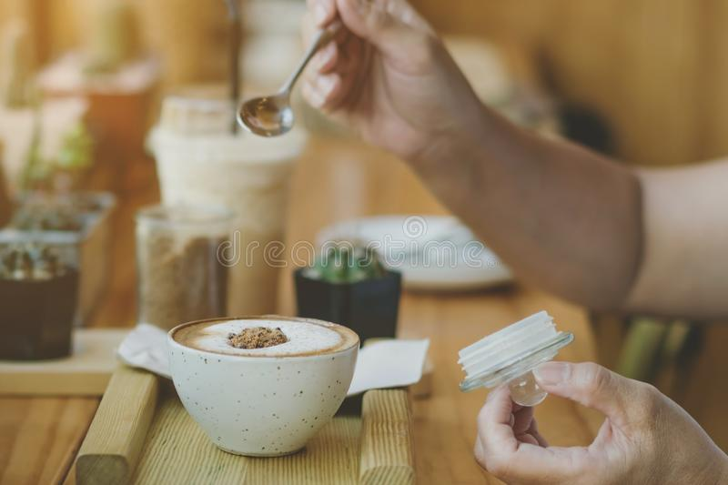 Woman pouring sugar into a cup of coffee. Woman pouring sugar into a white cup of coffee royalty free stock photo