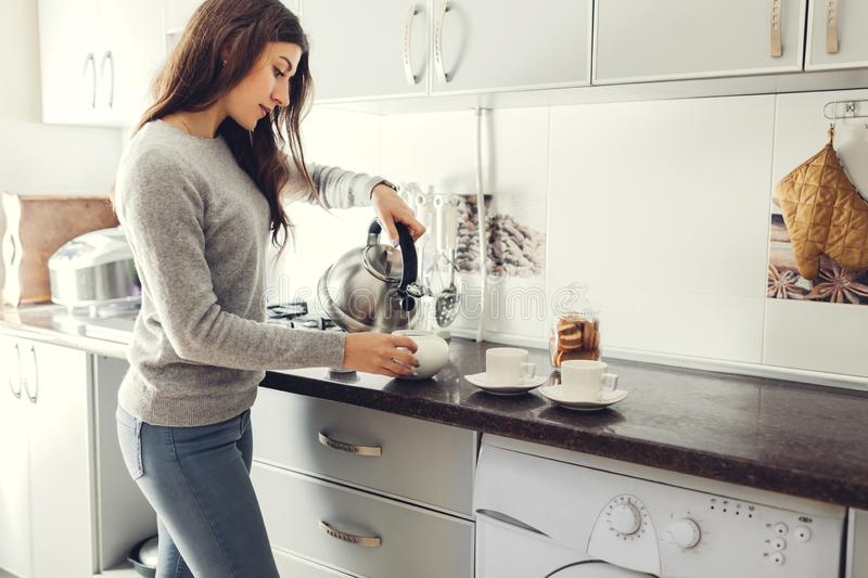 Woman pouring tea into ceramic cup at table.  stock images