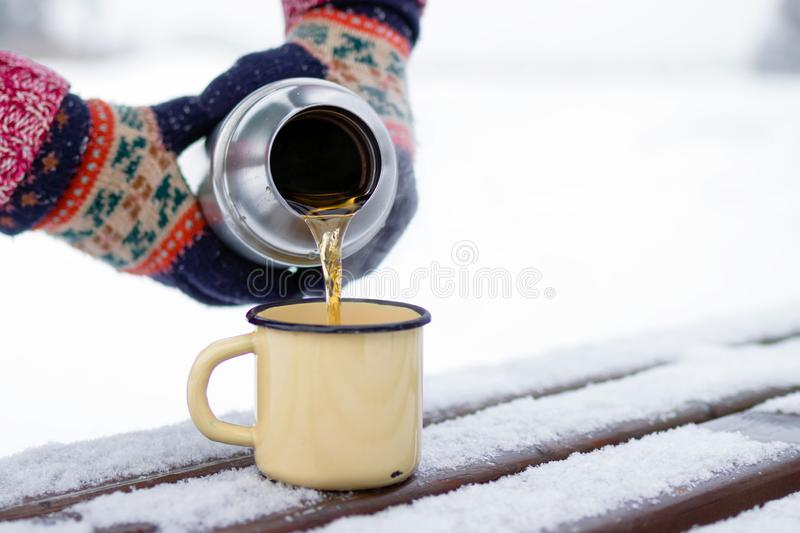 Woman is pouring tea from thermos into cup on a walk in winter park royalty free stock photography