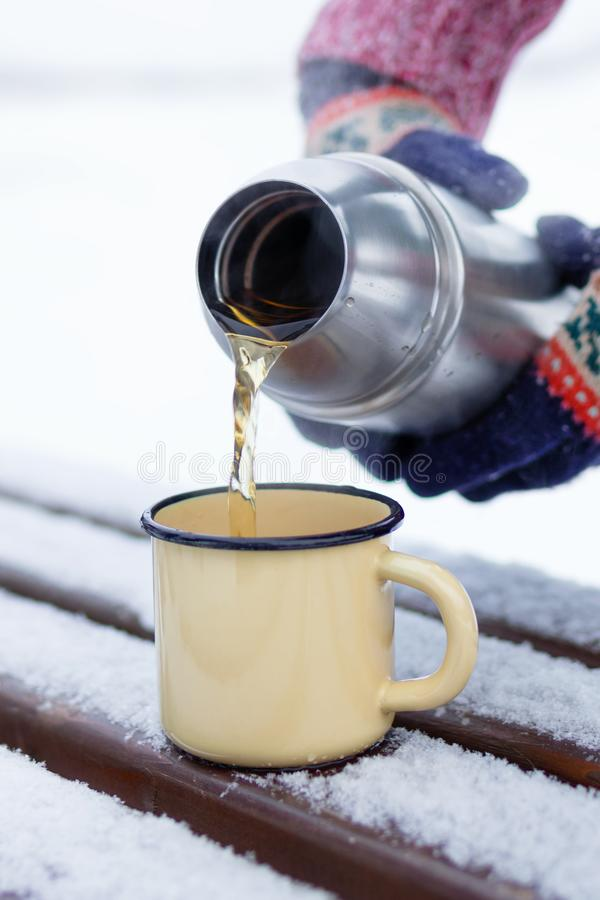 Woman is pouring tea from thermos into cup on a walk in winter park royalty free stock images