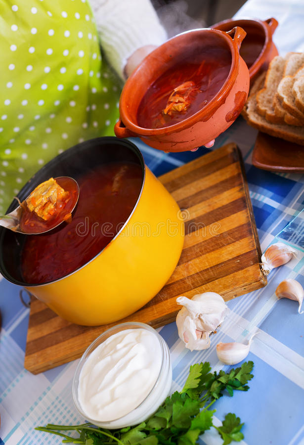 Woman pouring Traditional Russian cooked soup stock photography