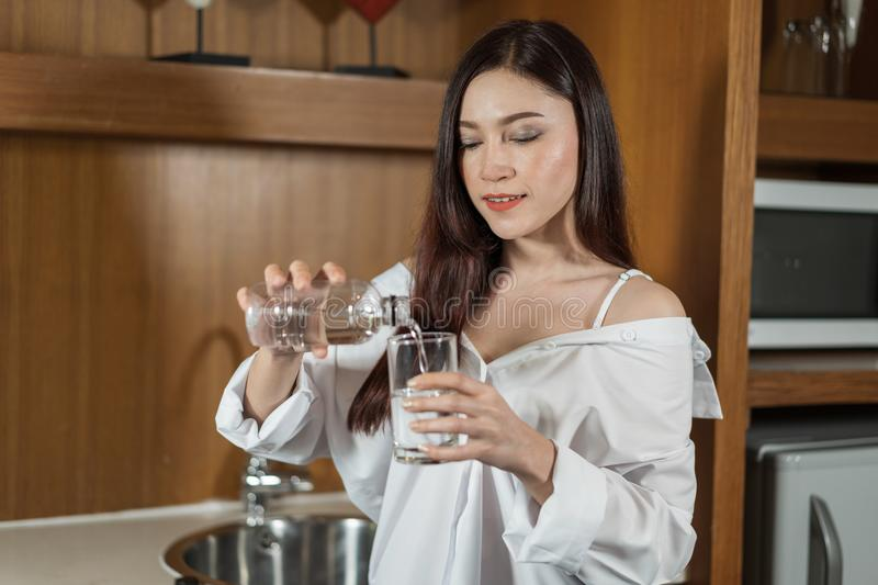 Woman pouring water from bottle to glass stock photo