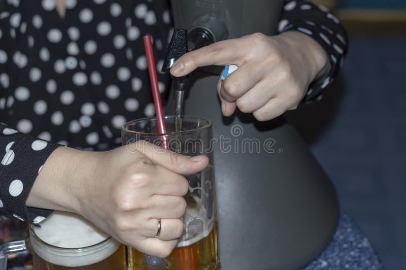 Woman pours fresh cold beer from a tabletop cooling dispenser into beer glasses royalty free stock photography