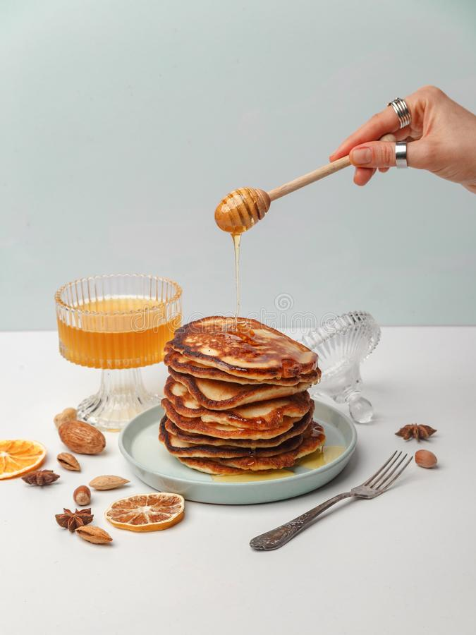 Woman pours honey on pancakes. The concept of a delicious breakfast royalty free stock photography