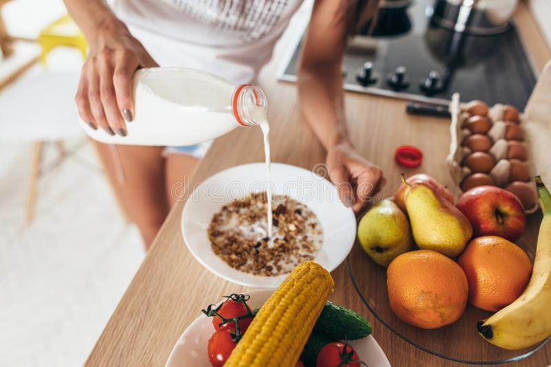 Woman pours milk into a bowl. Muesli fruits vegetables. royalty free stock images