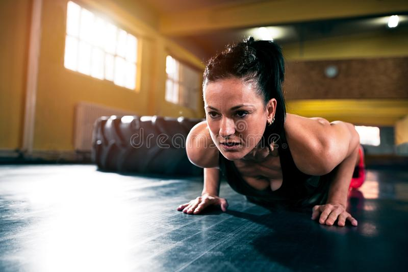 Woman power muscular machine doing push ups at gym. Woman powerfull muscular machine doing push ups at gym close up royalty free stock images