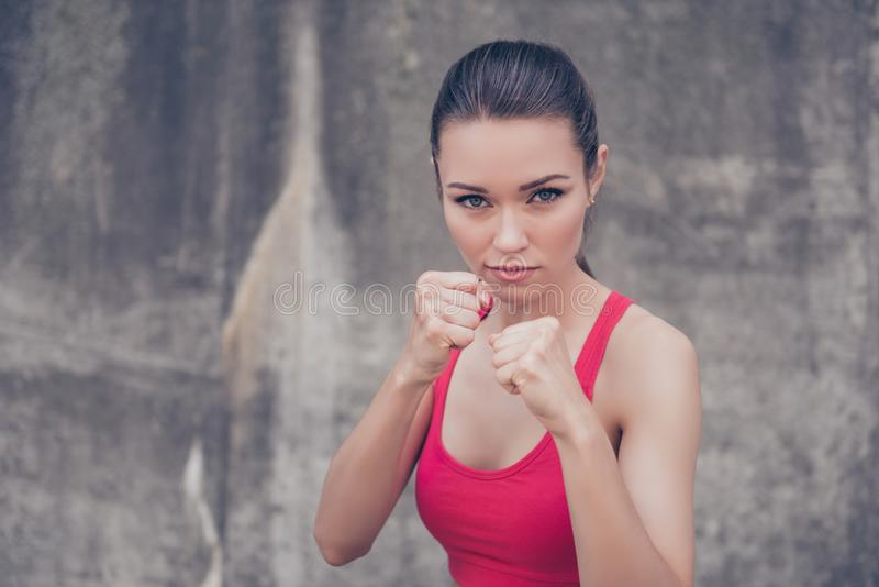 Woman power, self defence concept. Close up portrait of attractive serious fit boxer, ready for fight, on concrete wall royalty free stock photos