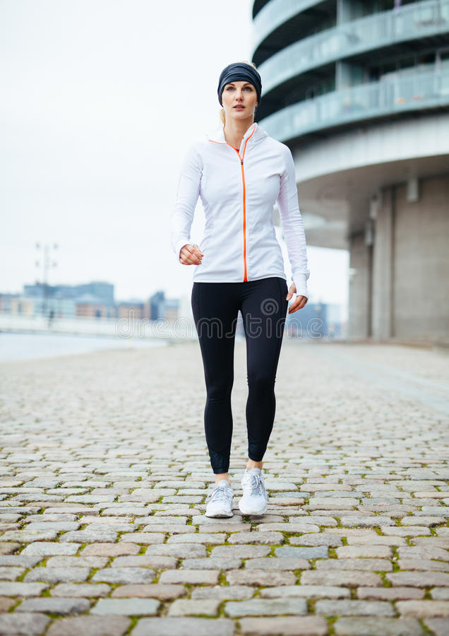 Woman power walking on urban street. Full length portrait of a pretty young woman in sportswear exercising outdoors. Woman power walking on urban street stock photography