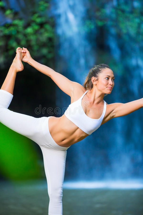 Woman Practacing Yoga in front of Beautiful Waterfall stock images