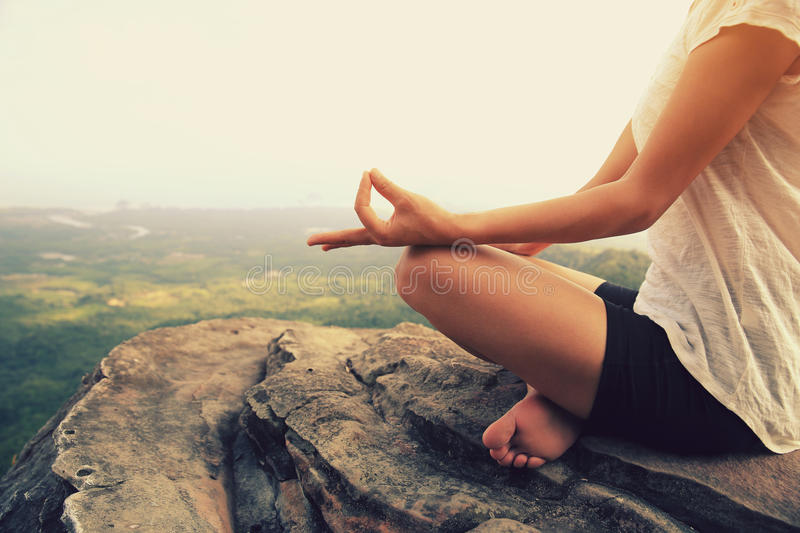 Woman practice yoga at mountain peak cliff. Young woman practice yoga at mountain peak cliff royalty free stock image
