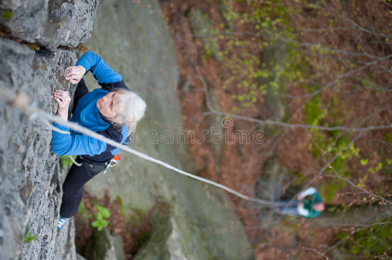 Woman practices in climbing at the rock in the mountains. Another man belay on the ground. Close-up view from above royalty free stock images