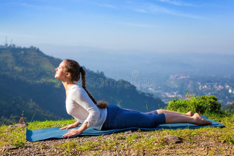 Woman practices yoga asana bhujangasana cobra pose stock photography