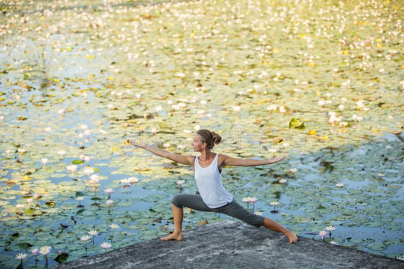 Woman practices yoga on a lake with lotus water lilies.  royalty free stock photo
