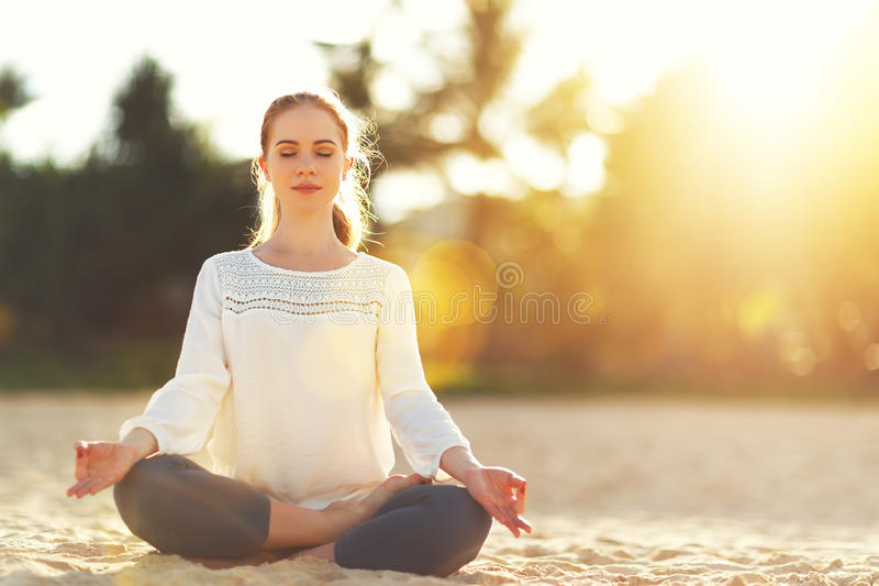 Woman practices yoga and meditates in lotus position on beach stock photos