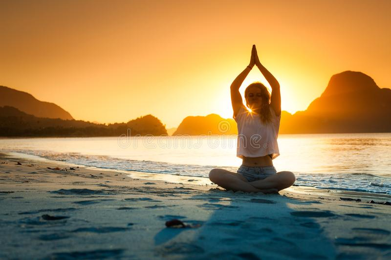 Woman practices yoga and meditates on the mountain. stock photos
