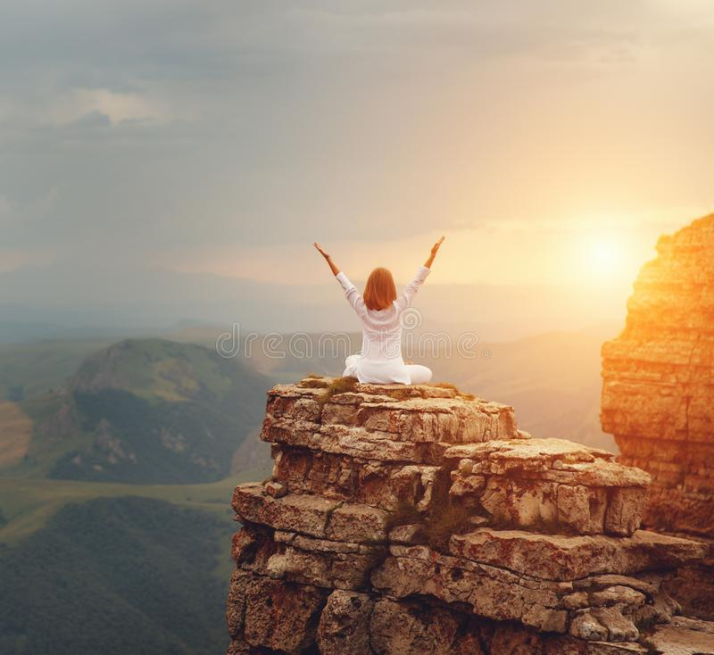 Woman practices yoga and meditates on mountains stock photos